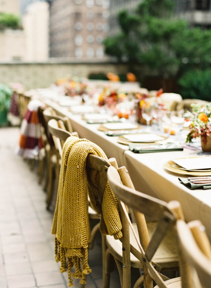 outdoor wedding table with cosy warm blankets on chairs