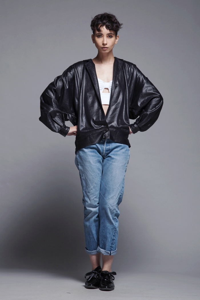 woman with oversize leather bomber jacket on grey background