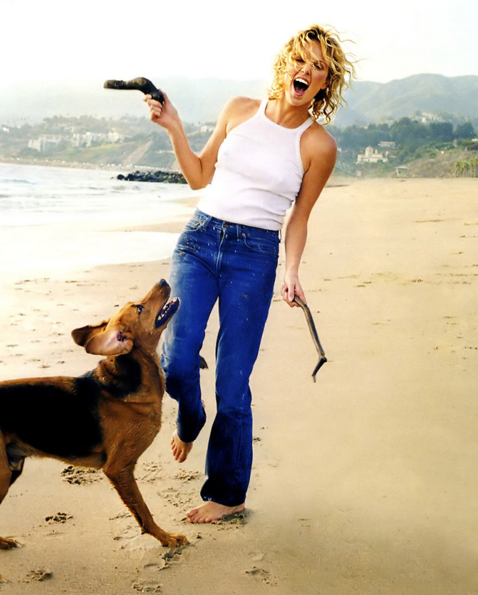 Woman in jeans and white top laughing and playing with a dog on the beach
