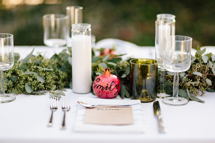 elegant fall wedding table with pomegranate place signs and candles