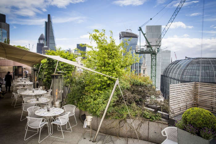 Coq d'Argent rooftop restaurant terrace with white tables overlooking the city