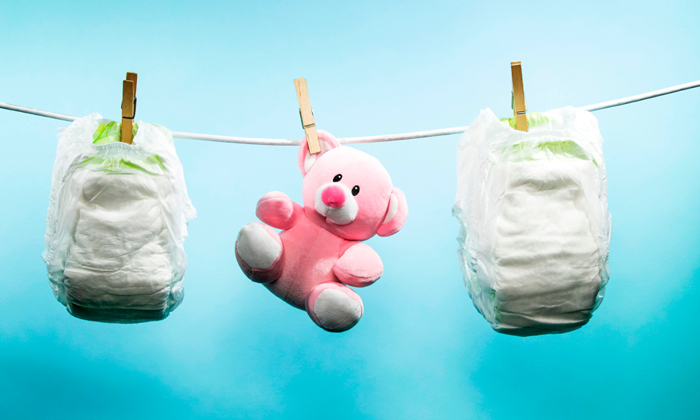 two diapers and pink teddy bear hanging