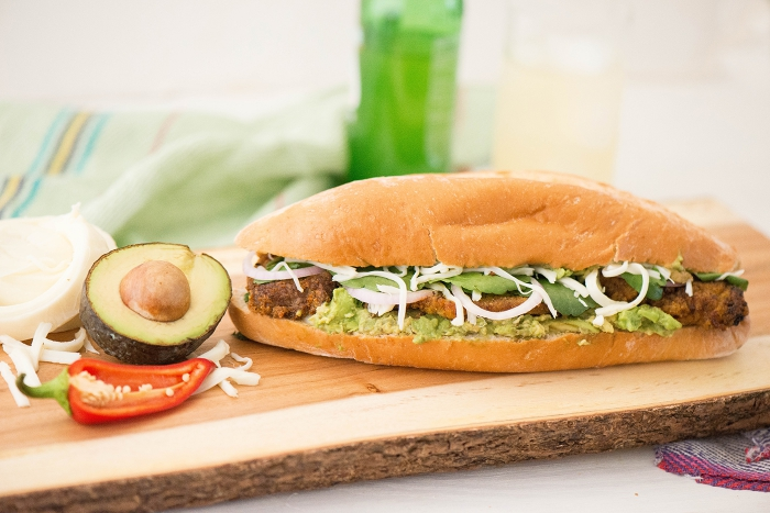 Mexican loncha sandwich on a wooden board with half avocado and chili pepper