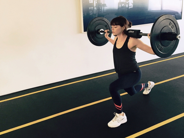 Emma Stone dressed in black sportswear intense workout heavy weight lifting in a gym