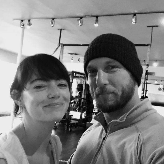 Emma Stone smiling at the camera with fitness instructor at the gym