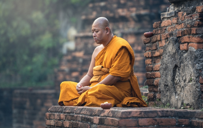 Buddhist monk dressed in orange meditating at the walls of a temple