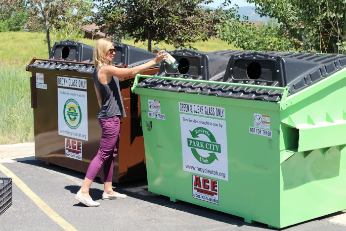 Woman throwing plastic in container to recycle