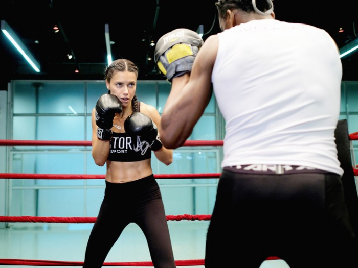 woman with boxer braids on a boxing ring against a man