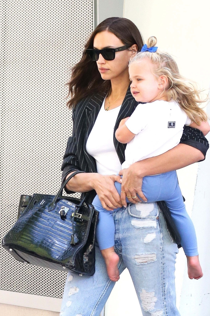 irina shayk walking outside with her daughter in hands