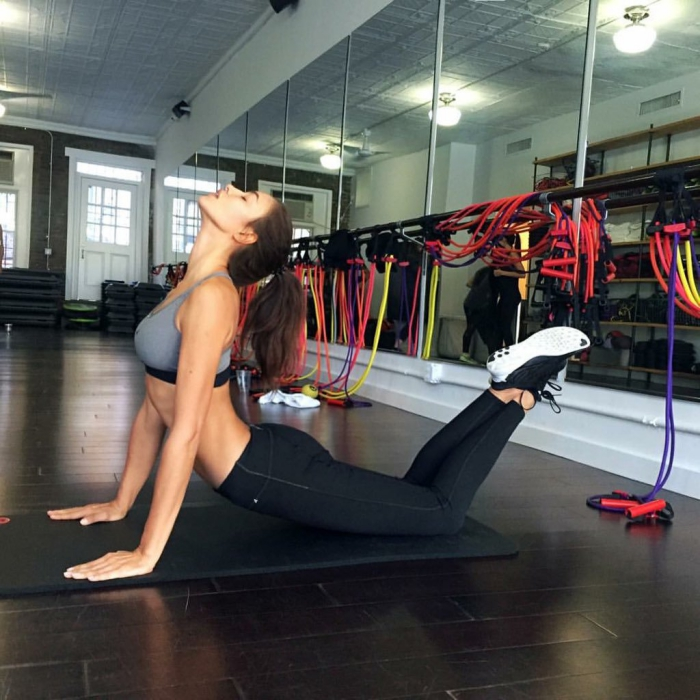woman in sportswear in the gym on a mat exercising