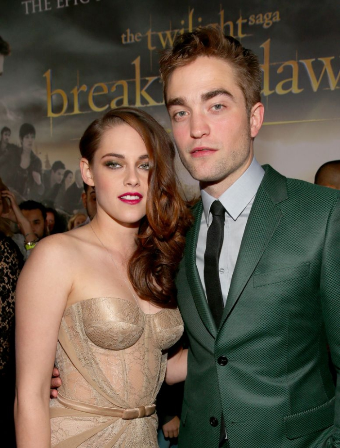 Kristen Stewart and Robert Pattison posing in front of a poster