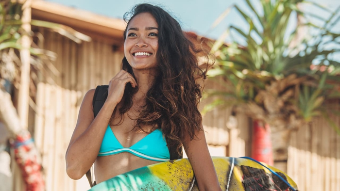 woman with lazy waves in her hair and bright swimsuit carrying surfboard