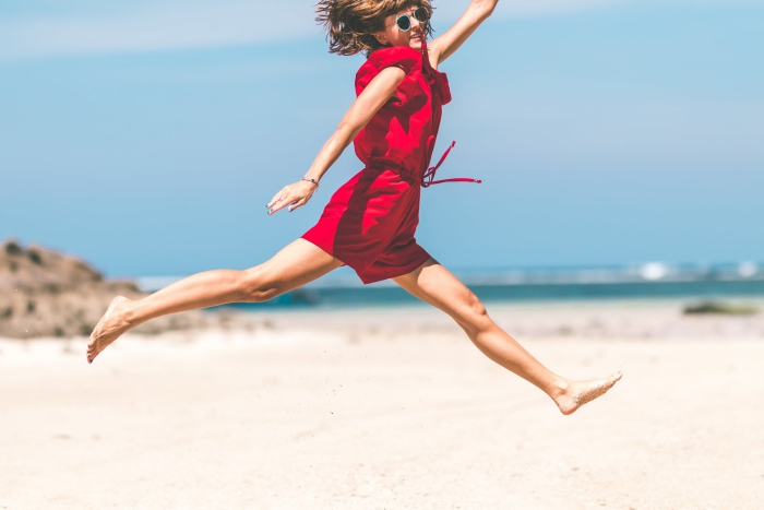 Woman in red dress jumping on beach