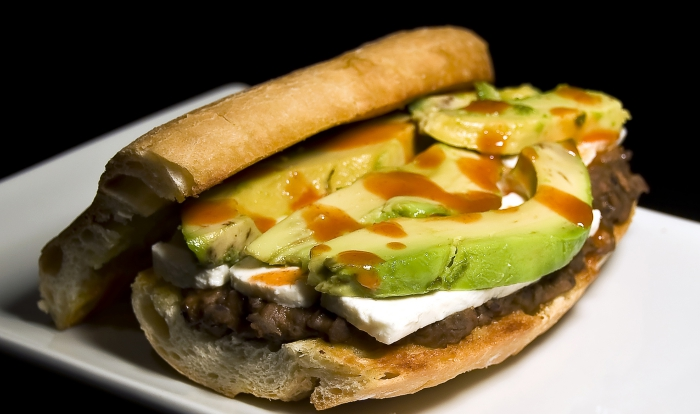 Mexican loncha sandwich with meat and avocado closeup