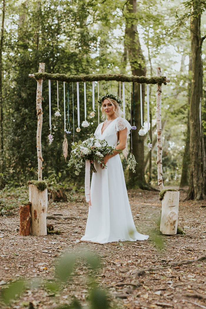 Outdoor bohemian wedding bride with forest in the backdrop