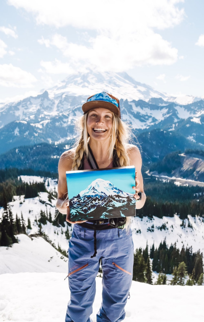 Rachel Pohl in the mountains showing her painting