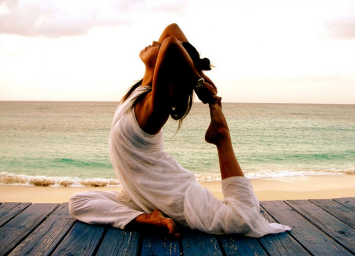 Spiritual practices woman dressed in white doing yoga on the beach