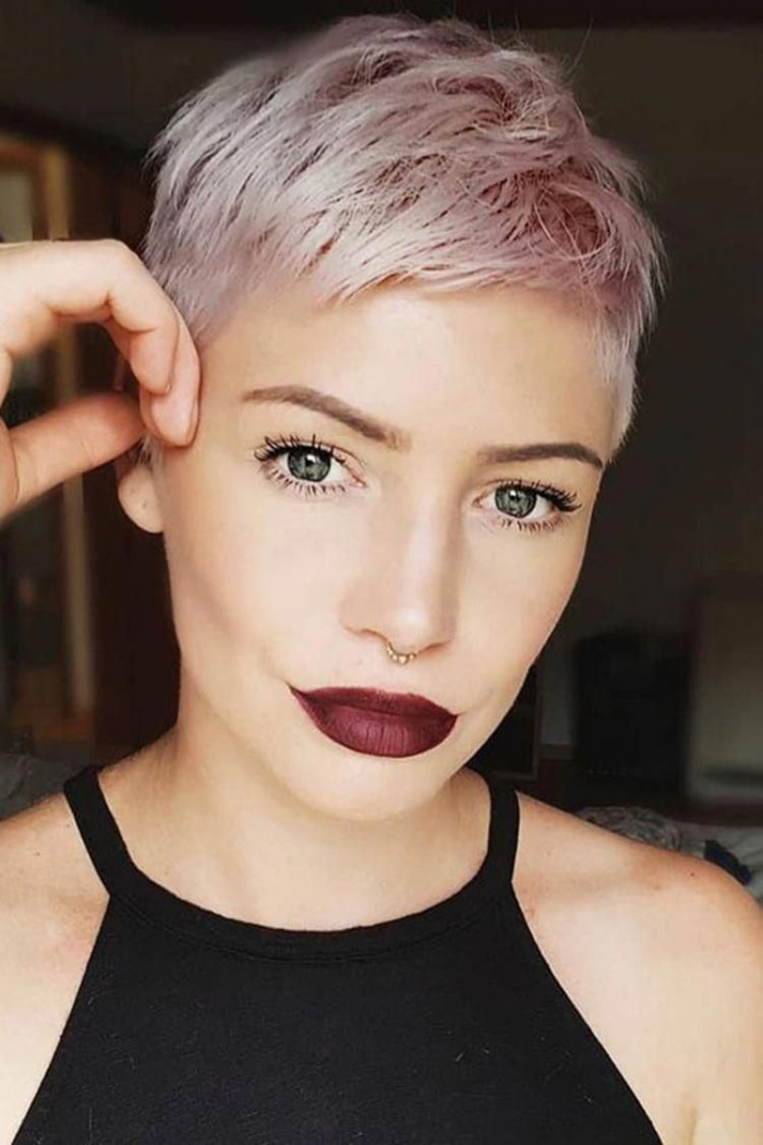 Woman with super short pink pixie hair looking in the camera deep red lipstick