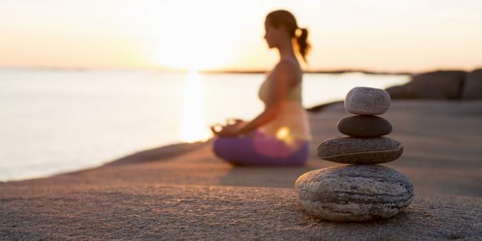 Woman meditating at sunrise on a lake shore- stones close up