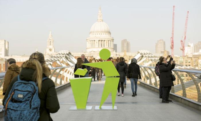 green Tidyman sign on bridge with people