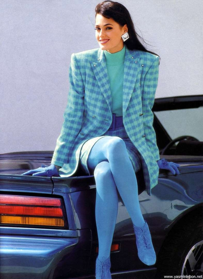Retro model woman sitting on a car dressed in light blue blazer with shoulder pads