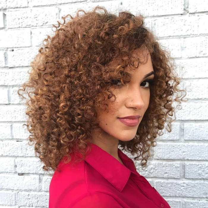 Woman dressed in bright shirt with curly hair