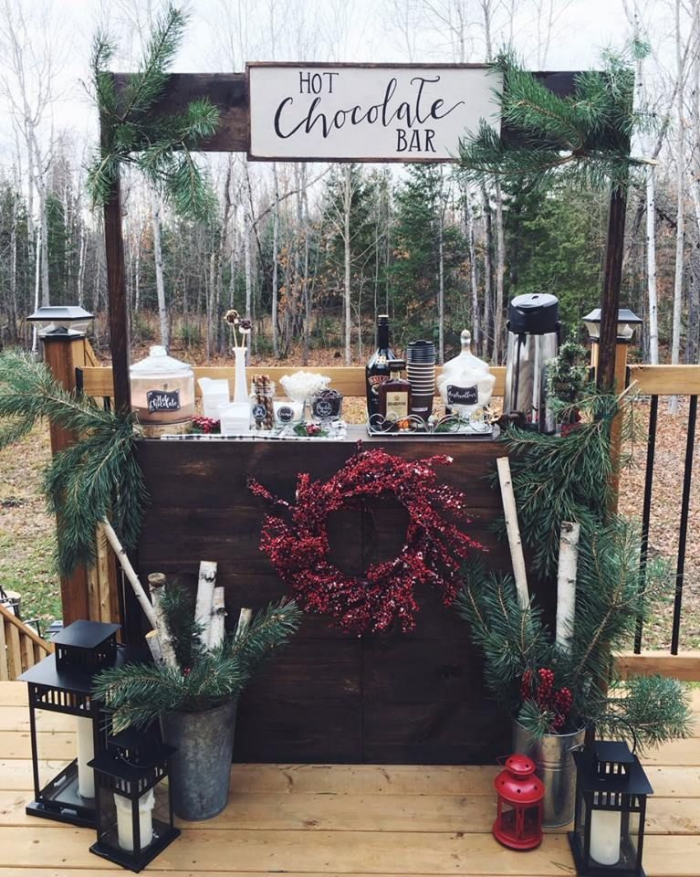 Outdoor wedding decor hot chocolate bar decorated with pine branches