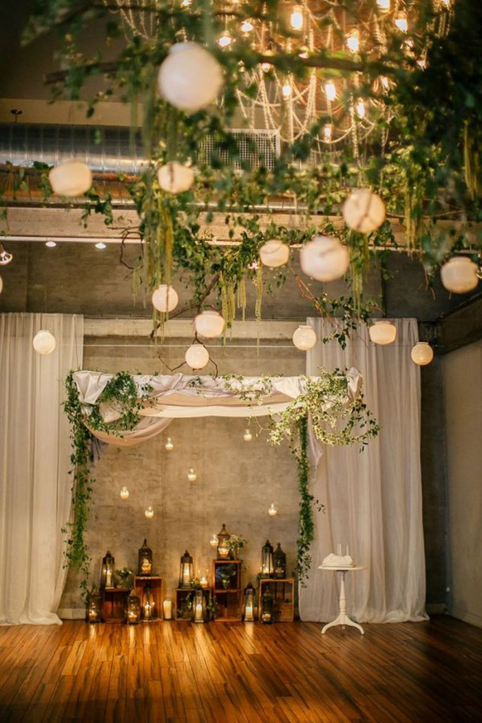 wedding reception décor indoors backdrop branches foliage lanterns and outdoor lights