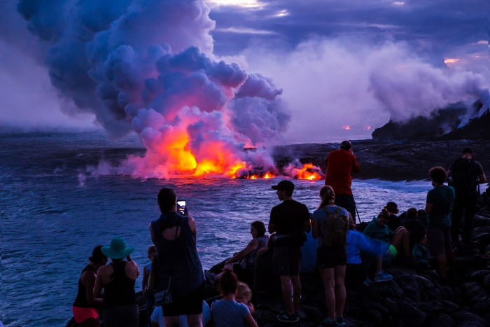 People taking pictures of lava river meeting the ocean