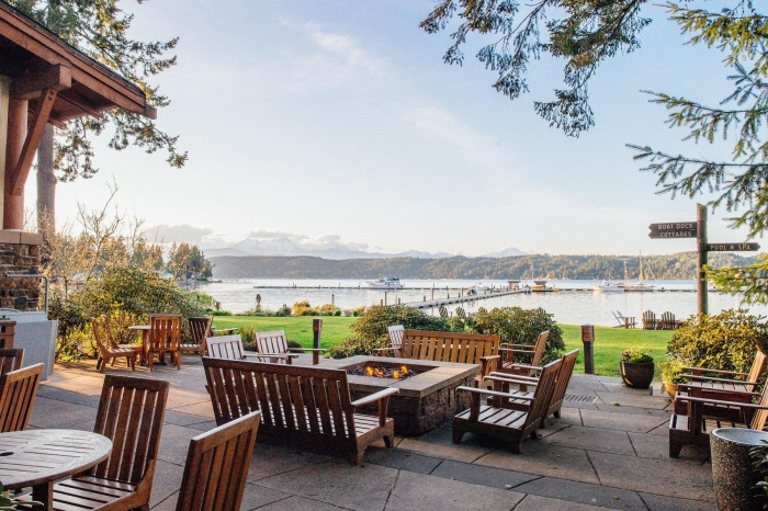 large terrace with wooden furniture and fire pits beautiful view on lake