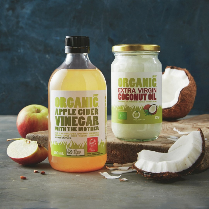 organic apple cider vinegar in glass bottle and Coconut Oil in glass jar with coconut and apples