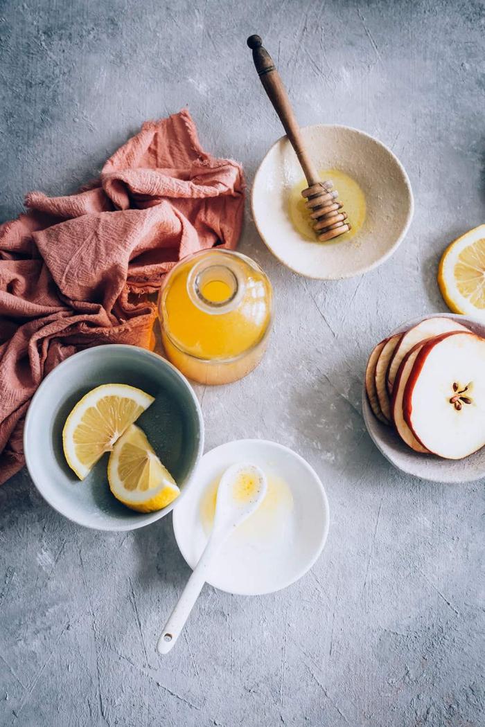 Apple Cider Vinegar bottle slices of lemon slices of apple honey