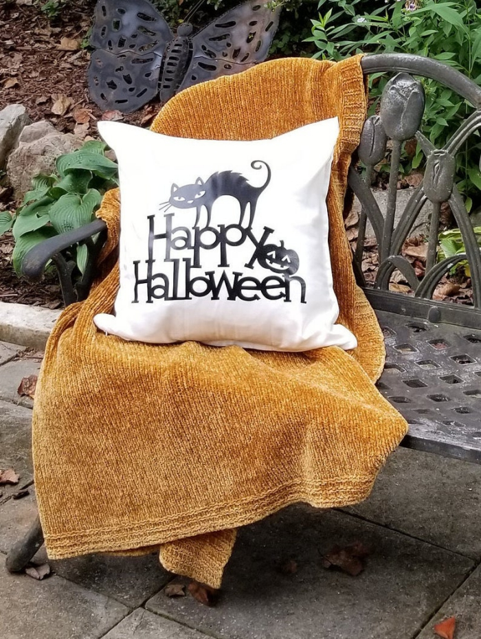 Halloween home decor cushion cover with black cat on a bench with a blanket