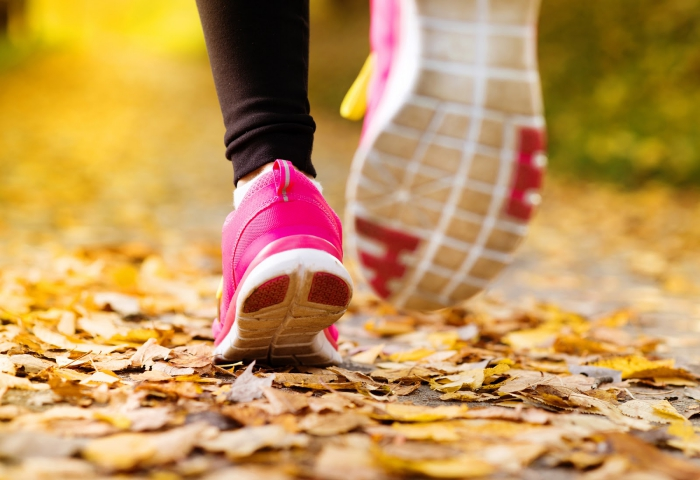 Woman jogging in a park fallen leaves pink running shoes