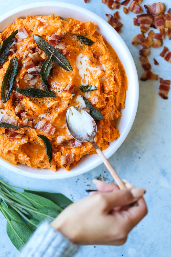 hand adding milk with a spoon close up mashed sweet potatoes with spices and bacon
