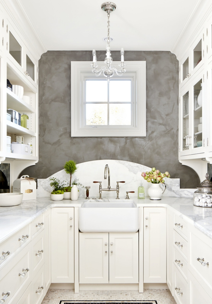 beautiful white and grey galley kitchen with a chandelier