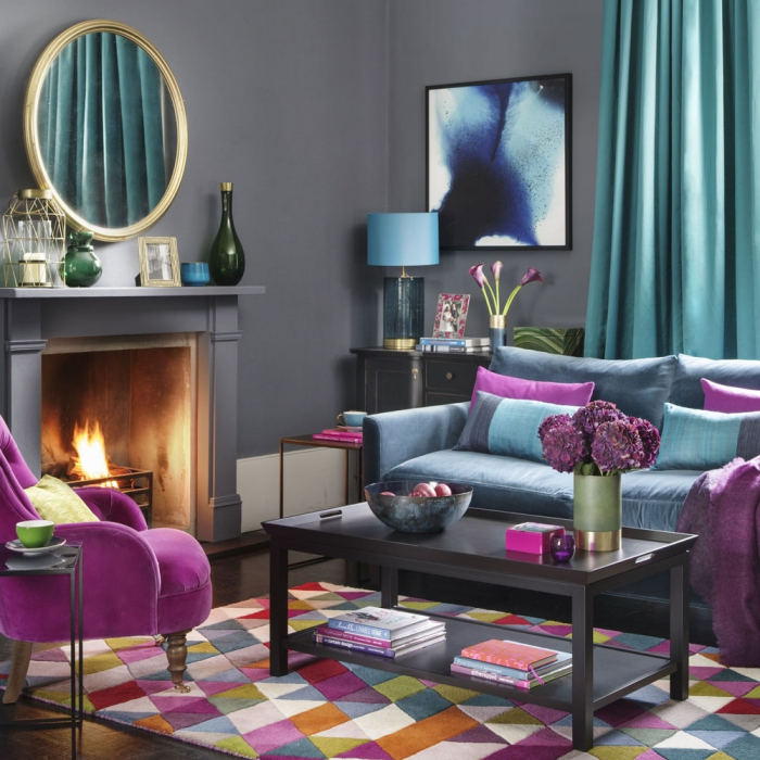 Grey living room with bright colorful accents purple chair blue curtains and a fireplace