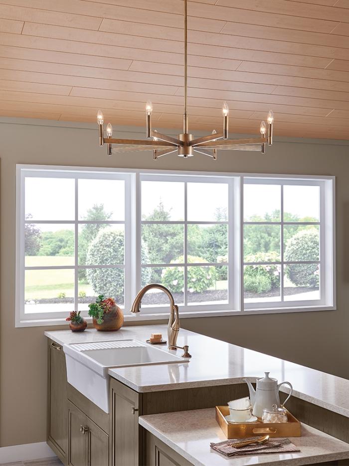 Sleek modern metallic gold kitchen chandelier in a minimalist kitchen interior