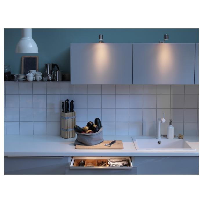 Modern minimal metal kitchen cabinet lights in a small white kitchen