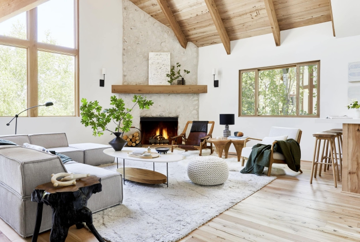 Modern living room in Scandinavian style with wooden ceiling and floor, fireplace and soft carpet
