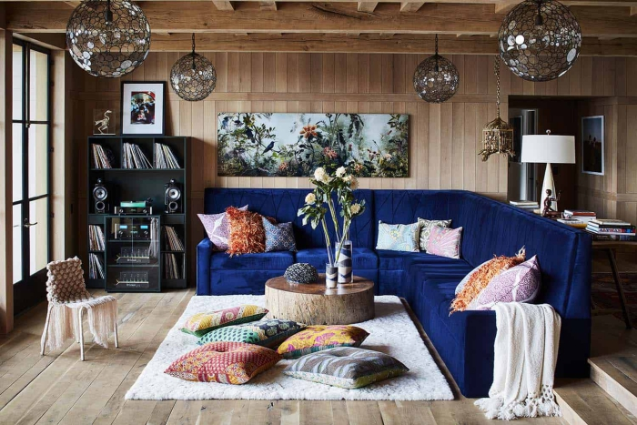 modern living room with wooden walls and floor and dark blue sofa