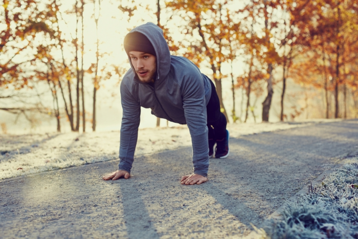 Young runner dressed in grey doing push ups exercise during cold autumn morning