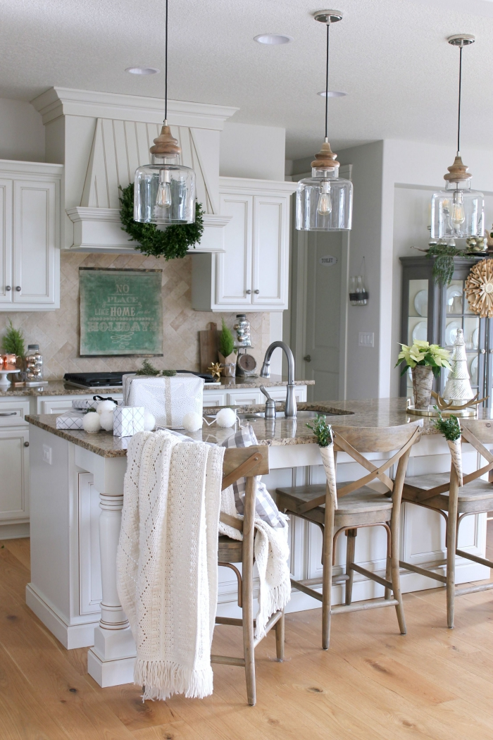 Three pendant lights over kitchen island in white traditional style kitchen interior