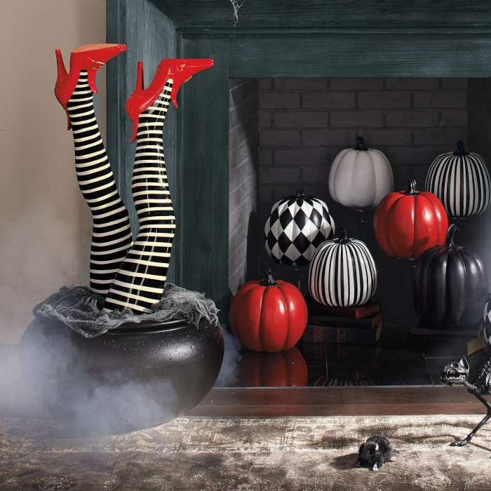 Indoor Halloween decor with colorful pumpkins in a fireplace and legs in a pot