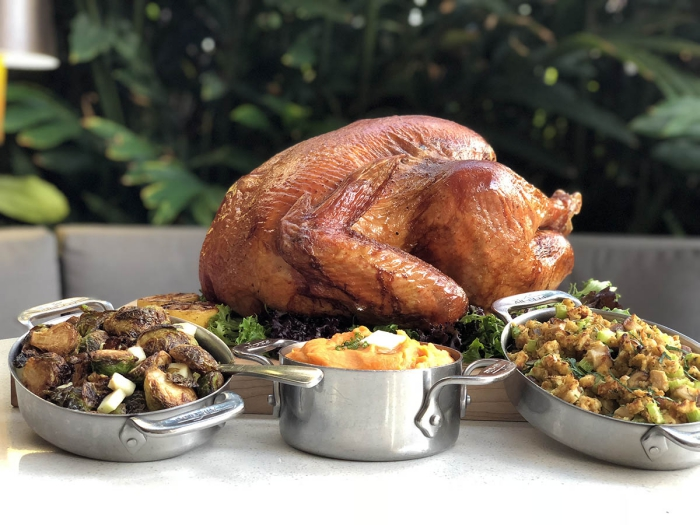 Thanksgiving turkey with different side dishes on a table with greenery in the background