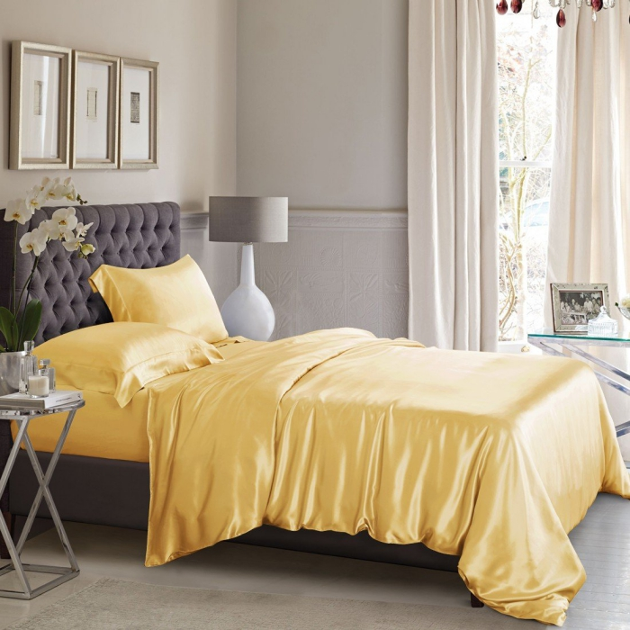 bed in a light room with light yellow high quality silk bedding