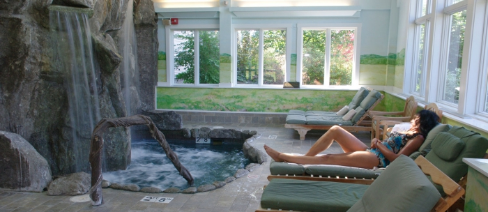 woman relaxing at an indoor spa area with stone indoor waterfall
