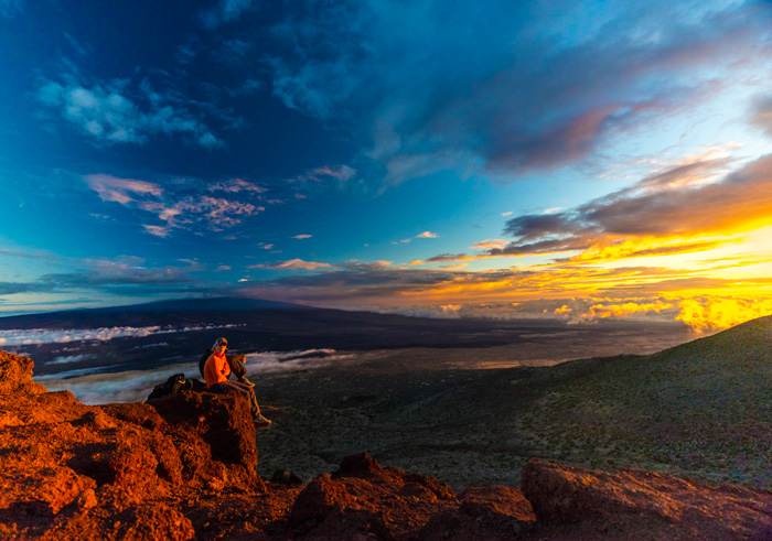 Man watching the sunset from a rock rocky landscape colorful sky