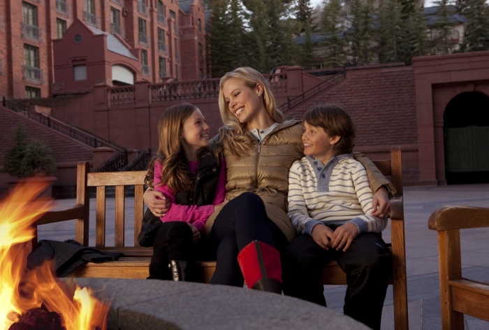 Mom sitting with children boy and girl in front of the outdoor fire