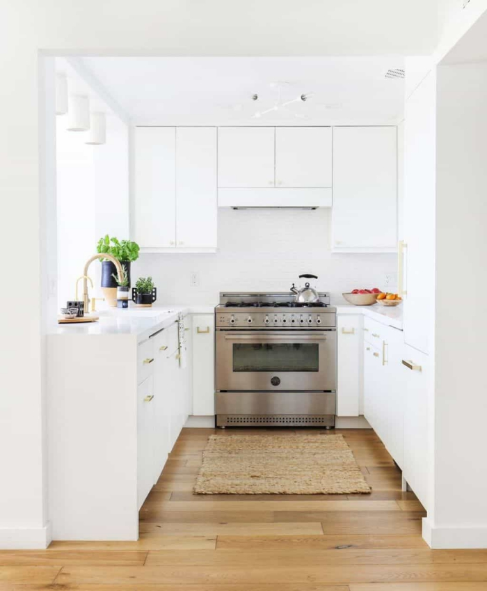 all white u-shaped kitchen with a wooden floor